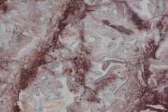 Classic travertine texture. Reddish brown structure with fractures and gray spots. Used as a background. Stock Image