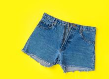 Classic Trendy Women Jeans Denim Shorts with Fringes on Bright Yellow Background. Flat Lay. Street Summer Fashion Sale Lifestyle. Travel Vacation Concept Stock Photography