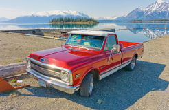 A classic truck with the rocky mountains reflected in a lake Royalty Free Stock Image
