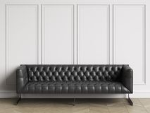 Classic tufted sofa in black leather  in classic interior with copy space. Classic tufted sofa  in classic interior with copy space.White walls with mouldings Stock Photography