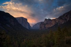 Half Dome rock climbing summits in beautiful golden light at su. Classic Tunnel View of scenic Yosemite Valley with famous El Capitan and Half Dome rock climbing royalty free stock photo