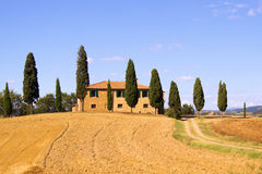 Classic Tuscany. Classic Tuscan landscape with stone house and row of cypress trees Royalty Free Stock Image