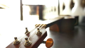Classic ukulele on leather sofa. Pan shot stock video footage