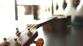 Classic ukulele on leather sofa. Tilt down shot stock footage