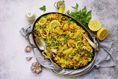 Classic valencian paella from rice with seafood and green pea -. Traditional dish of spanish cuisine in a frying pan on a light slate, stone or concrete Royalty Free Stock Photos