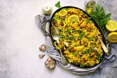 Classic valencian paella from rice with seafood and green pea -. Traditional dish of spanish cuisine in a frying pan on a light slate, stone or concrete Royalty Free Stock Images