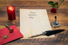 Classic Valentine`s Day cad with decorative quill and stand, red envelop with wax seal, red candle and rose, space for your text stock photography