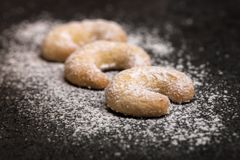 Classic vanilla kipferl with icing sugar. Close-up, dark background stock images