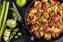 Classic version of thanksgiving or christmas Stuffing. Made with bread, celery, onions, apples, chestnuts, thyme and sage in a black casserole with ingredients royalty free stock photo