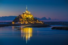 Mont Saint-Michel in twilight at dusk, Normandy, France. Classic view of famous Le Mont Saint-Michel tidal island in beautiful twilight during blue hour at dusk Royalty Free Stock Photo