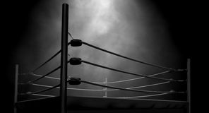 Classic Vintage Boxing Ring. An old vintage boxing ring surrounded by ropes spotlit in the middle on an isolated dark background Royalty Free Stock Image