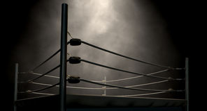 Classic Vintage Boxing Ring. An old vintage boxing ring surrounded by ropes spotlit in the middle on an isolated dark background Stock Photos