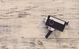 Classic vintage old 8mm movie camera on old wooden boards. Hipster style. Top view with copy space. Free space for text. Royalty Free Stock Photos