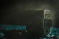 Classic vintage old 8mm movie camera on table with fog close up. Selective focus. Old Soviet Camera Stock Images