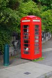 Classic vintage red British telephone booth. A classic vintage red British telephone booth on the sidewalk in Edinburgh, Scotland. Many of these iconic phone Stock Photos