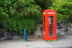 Classic vintage red British telephone booth. A vintage red British telephone booth stands by the roadside in Edinburgh, Scotland. Many of these iconic booths Stock Photos