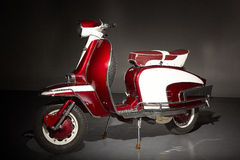 Classic vintage red scooter side view. Side view of a classic red and white motor scooter. Spare tire, chrome, red and white trim, vintage Italian style and Royalty Free Stock Photos