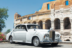 Classic vintage white wedding car at famous Colosseum or Coliseum building wall background Royalty Free Stock Image