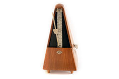 Classic vintage wooden metronome in motion. Old classic metronome  on white background Stock Images