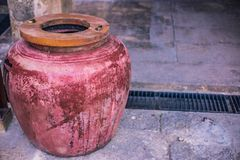 Classic water jar or red earthen jar. With wooden cover use for keep water make from ceramic and rock Stock Image