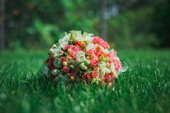 Classic wedding bouquet from roses, eustoma and freesia lies in the dense grass. Bright green and emerald summer photo. Wedding royalty free stock images
