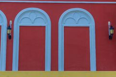 Classic white arch door pattern on the red wall background. Classic white arch door pattern on the red wall background of art and architecture Stock Image