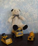 Classic Teddy Bears against a Blue Wall And Classic Construction Vehicles royalty free stock photos