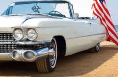 Classic white Cadillac at the beach. Classic white Caddie at the beach with American flag royalty free stock photos