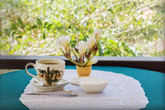 Classic white cup of black coffee decorated with flower and tree background. Classic white cup of black coffee decorated with flower on green nature background Royalty Free Stock Images