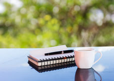 Classic white cup of black coffee with note and pen on green nat Royalty Free Stock Photos
