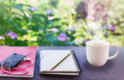 Classic white cup of black coffee with note and pencil on green Royalty Free Stock Image