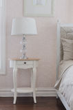 Classic white lamp on wooden white table in bedroom Royalty Free Stock Photography