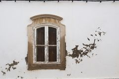 Classic window and a weathered white facade stock photography