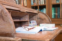 Classic antique wooden desk with books and laptop royalty free stock photography