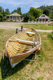 Classic wooden dinghy and colonial style houses Royalty Free Stock Image