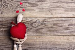 Classic wooden dummy holds red heart for Valentine`s Day. Old wooden background with space for text Royalty Free Stock Photography