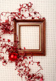 Classic wooden frame decorated with Christmas foil stars and red  ball Stock Photos