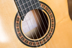 Classic wooden guitar. Close up of strings on classic or spanish handmade wooden guitar with butterfly roseta Stock Photography