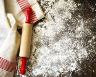 Classic wooden rolling pin and dusting of flour on wooden backgr Stock Images