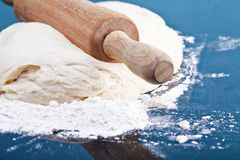 Classic wooden rolling pin with freshly prepared dough and dusti Stock Images