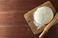 Classic wooden rolling pin with freshly prepared dough and dusting of flour on wooden background stock photography
