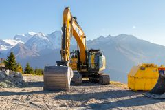 Classic Yellow Cat bulldozer Backhoe mountain sun stock photos