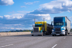 Classic yellow and blue modern semi trucks side by side on the r royalty free stock photo