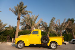Classic yellow Chevy pickup truck. Under the palm trees Stock Images