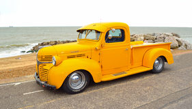Classic Yellow Dodge pickup truck. Felixstowe, Suffolk, England - August 27, 2016: Classic Yellow Dodge pickup truck on seafront promenade with sea in background stock images