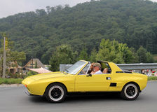Classic yellow italian sports car on downhill road Stock Image