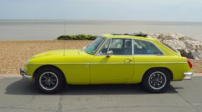 Classic Yellow MGB GT Motor Car Parked on Seafront Promenade. Royalty Free Stock Photography