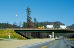 Classic yellow semi truck bulk trailers on bridge across interstate highway I-5 Oregon stock photos