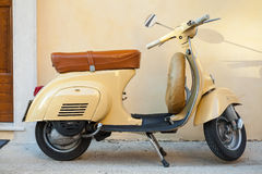 Classic yellow Vespa scooter near the wall Stock Photo