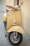 Classic yellow Vespa scooter parked near wall Royalty Free Stock Photography